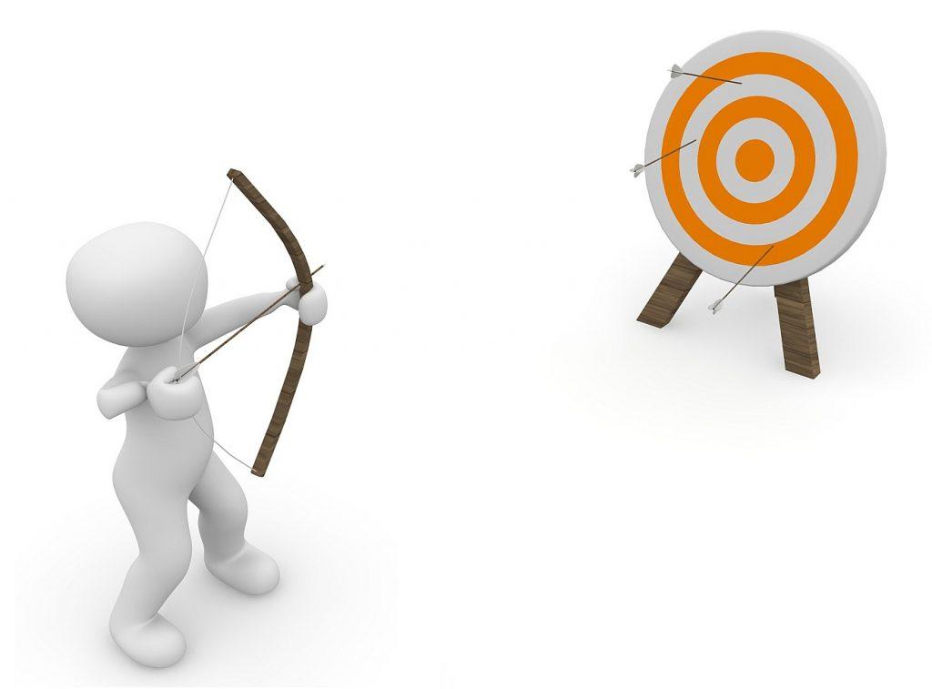 Ein Männchen schießt mit dem Bogen auf eine Zielscheibe, trifft aber nicht die Mite