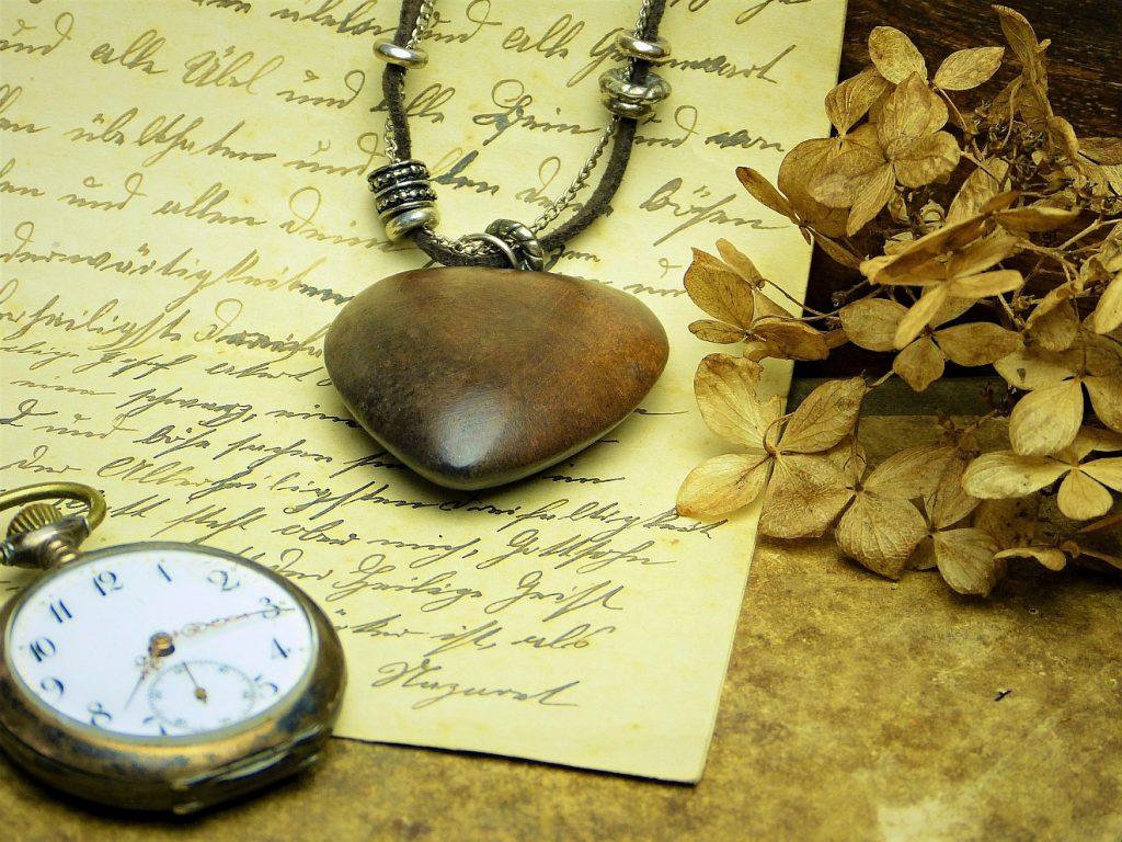 Eine Taschenuhr und ein Herz aus Holz an einer Halskette liegen auf einem handgeschriebenen Brief
