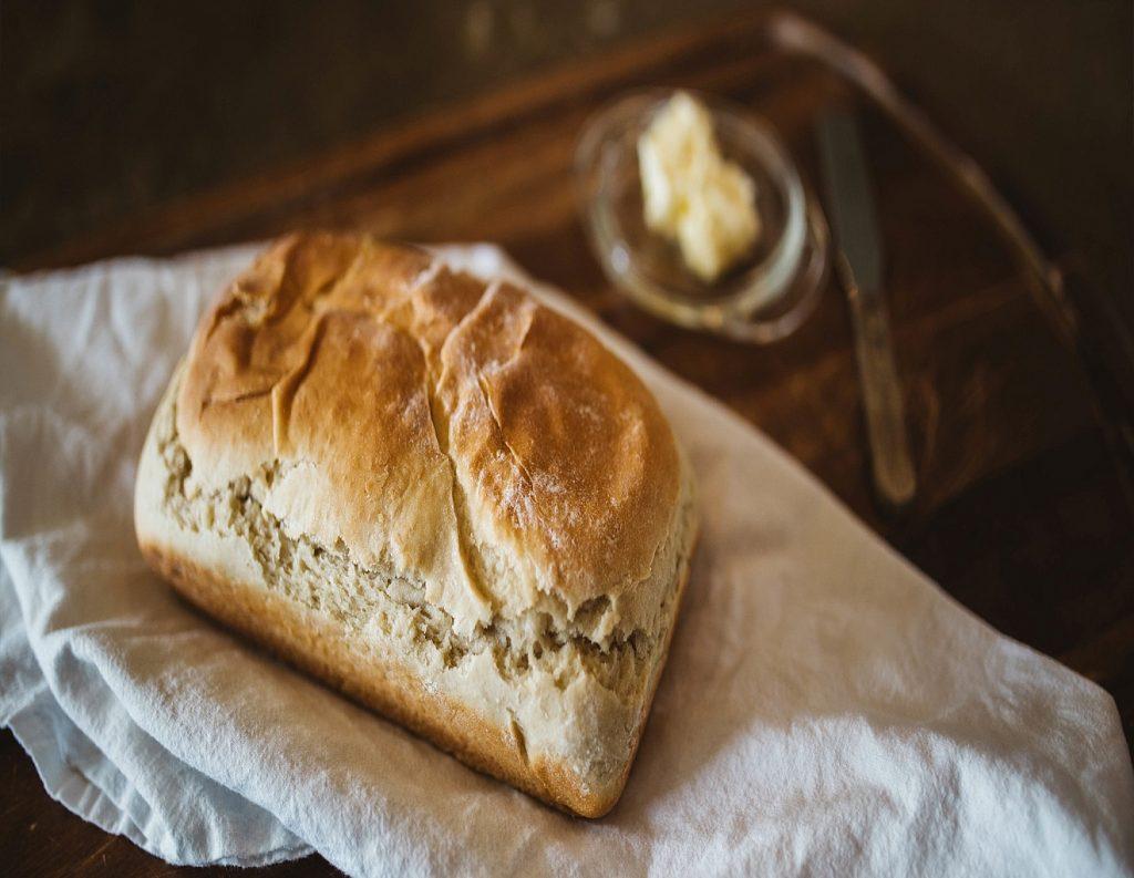 Ein kleines Brot auf einem Tuch, daneben ein Schälchen mit einem Klecks Butter und einem Messer