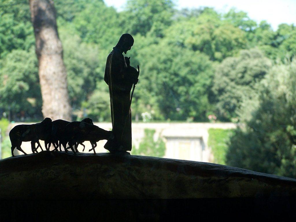 Der Große Hirte Jesus, gefolgt von seinen Schafen, als Silhouette einer Statue vor grünem Wald