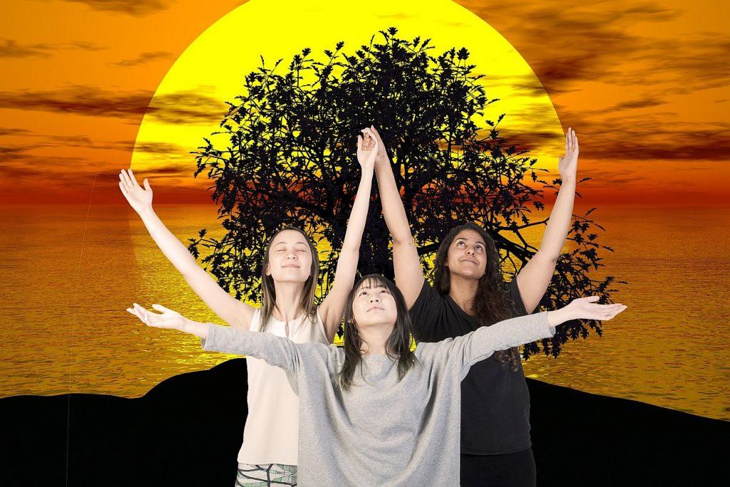 Drei Frauen strecken ihre Arme zur Seite und nach oben aus und freuen sich der Welt - hinter ihnen ist eine große Sonne zu sehen
