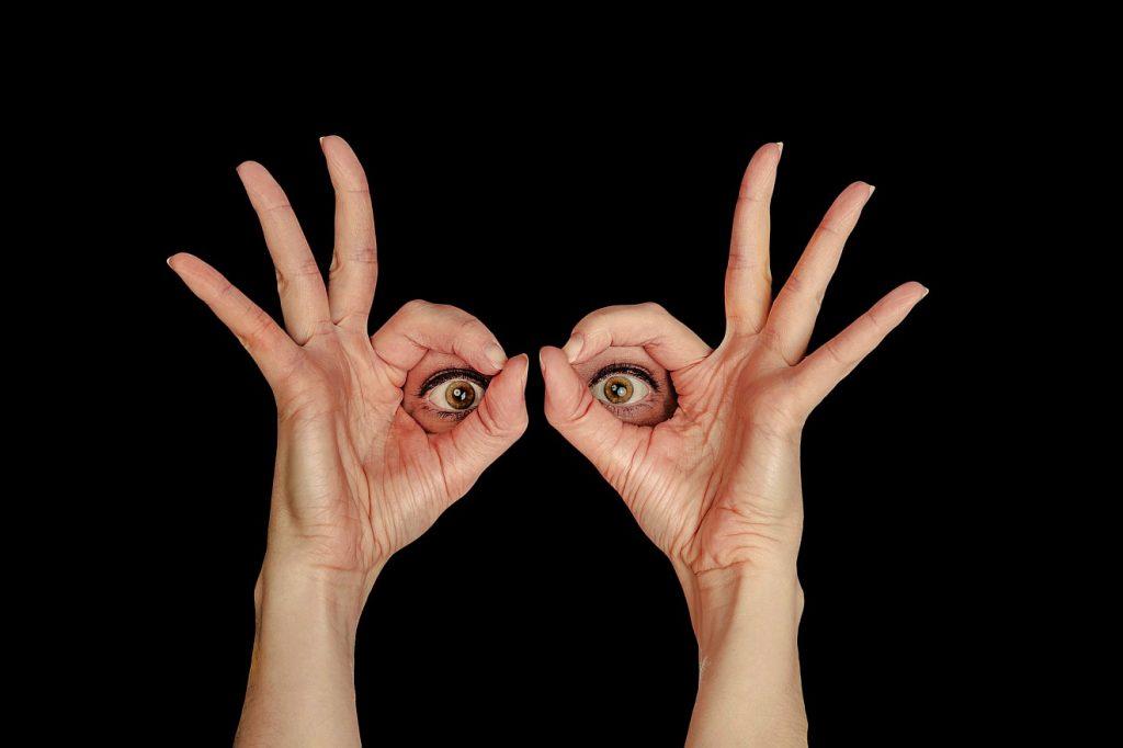Zwei Augen sehen aus schwarzem Hintergrund heraus durch zwei Hände hindurch, d. h. durch die von Zeigefinger und Daumen gebildeten Öffnungen