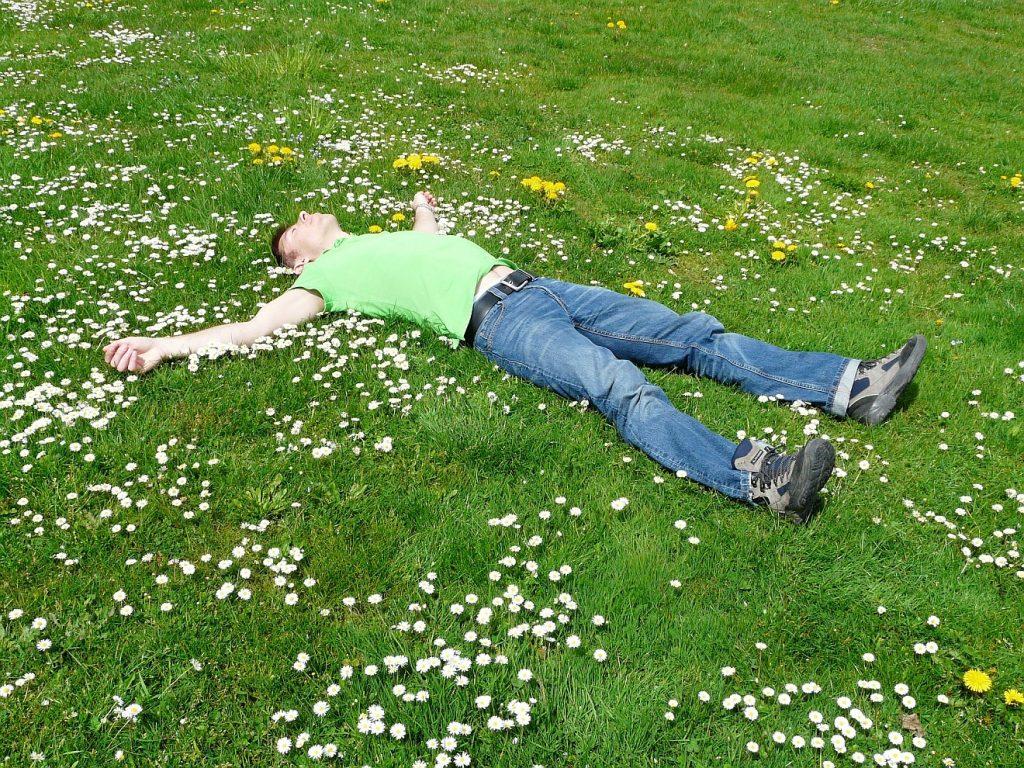 Ein Mann liegt ausgestreckt ganz entspannt auf einer Wiese mit Gänseblümchen und Löwenzahn - ein Bild für Gelassenheit?