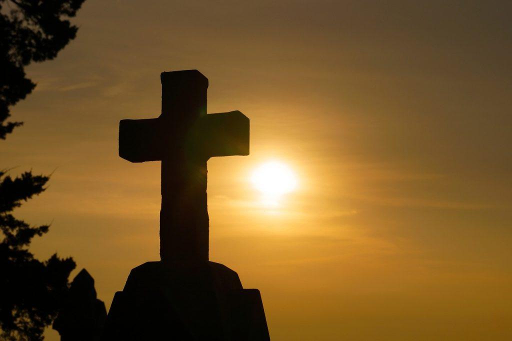 Ein Kreuz vor der unter- oder aufgehenden Sonne