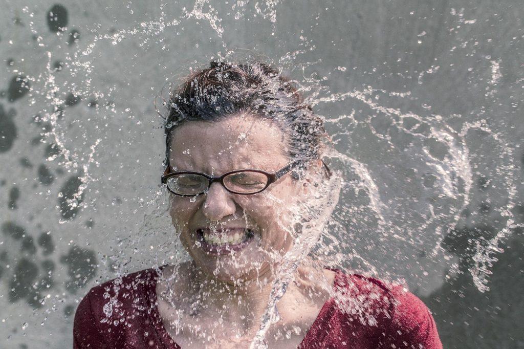 Eine Frau, der Wasser ins Gesicht gespritzt wird, was ihr offenbar gefällt - kalt ist besser als lau