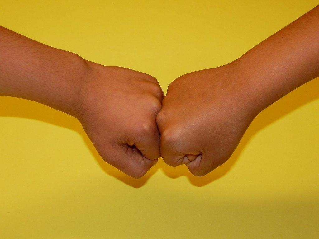 Die Fäuste zweier Kinder, vor gelbem Hintergrund aneinandergedrückt: ist Konfliktaustragung auch faustlos, mit Liebe, möglich?