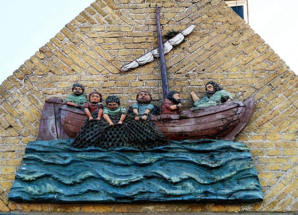 """Jesus sitzt im Boot mit fünf Jüngern oberhalb - """"auf der Tiefe"""" des wie ein Block gestalteten Wassers; die Jünger ziehen ein Netz mit Fischen aus dem Wasser"""