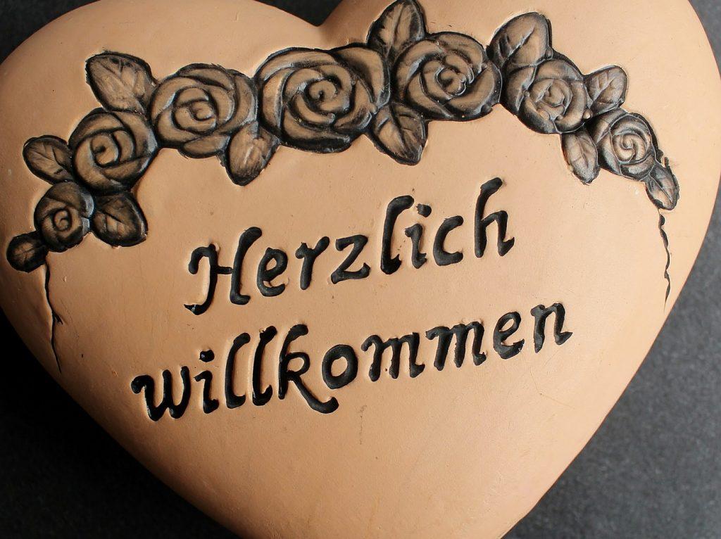"""Ein Herz aus Ton mit Rosen-Verzierung und der Aufschrift """"Herzlich willkommen"""""""