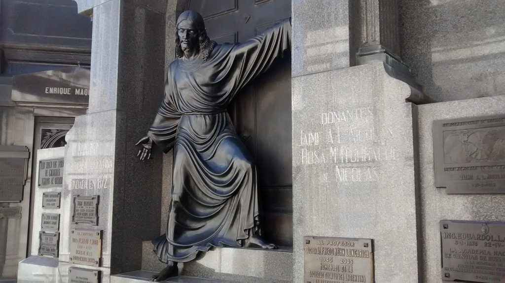 Jesus als Sieger über den Tod, dargestellt als Skulptur zwischen den Gräbern einer Urnenwand