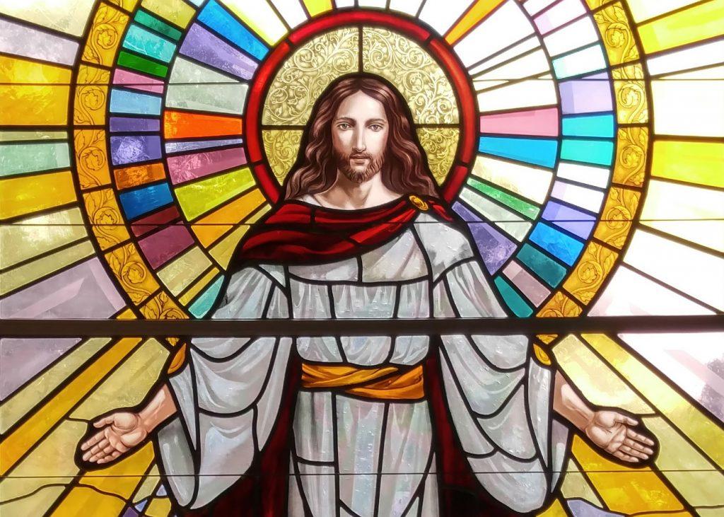 Jesu Gesicht umgeben von einem Strahlenkranz, seine Hände offen nach vorn ausgebreitet