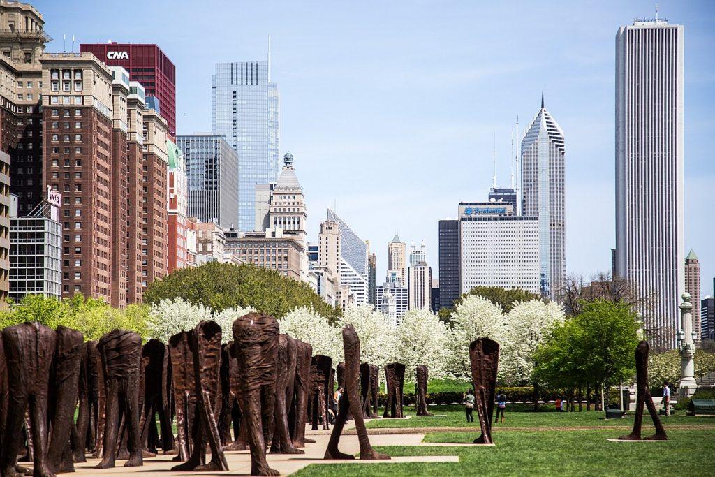 Die Skyline einer schönen Großstadt mit Hochhäusern verschiedener Bauart, Bäumen und großer Kunst im Park
