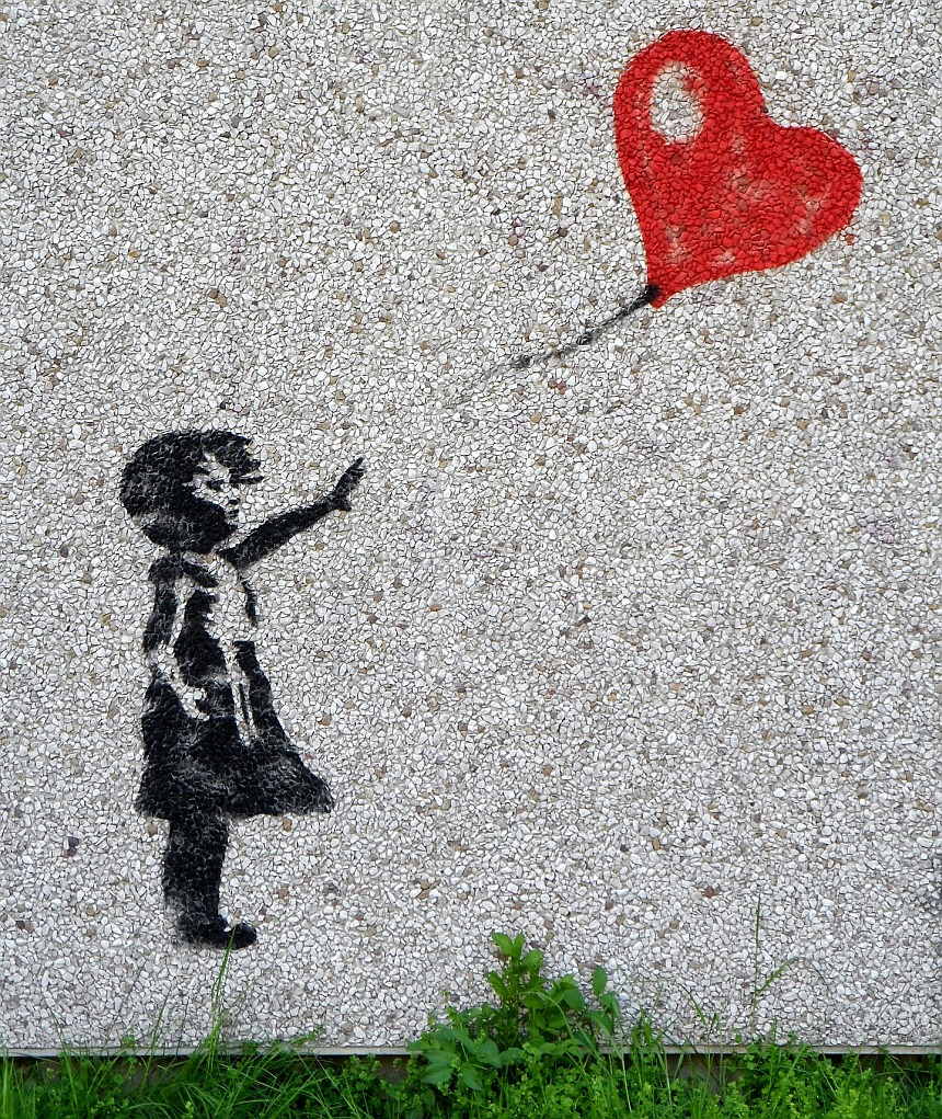 Ein Mädchen als Graffito an einer Waschbetonwand lässt einen herzförmigen Luftballon fliegen