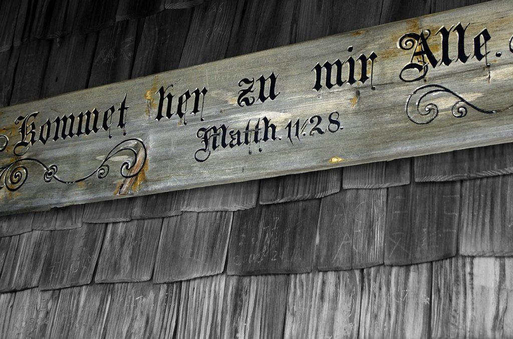 """Der Bibelspruch Matthäus 11, 28 an einer Hauswand: """"Kommet her zu mir Alle..."""""""