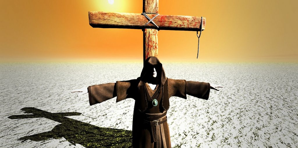 Ein Mann in Priestermantel und Kapuze steht mit ausgebreiteten Armen vor einem einfachen Holzkreuz in der Wüste unter einem gelben Himmel mit glühender Sonne