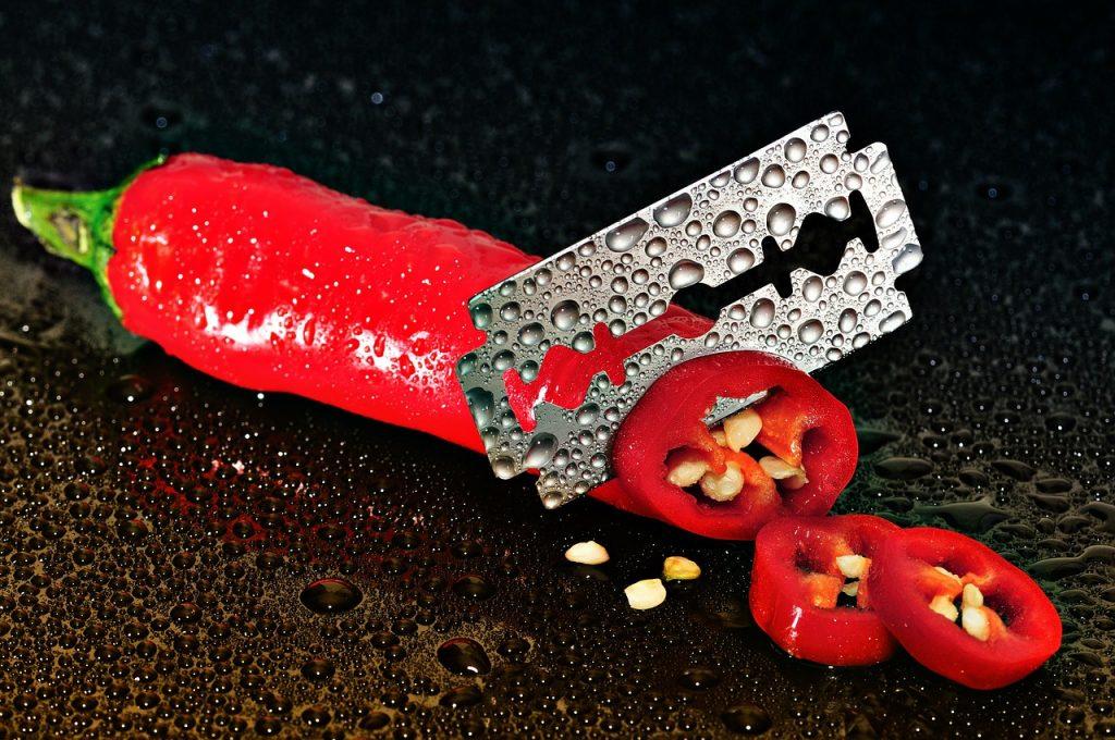 Eine rote Peperoni wird von einer Rasierklinge in Scheiben geschnitten: Symbol für scharfes Wort