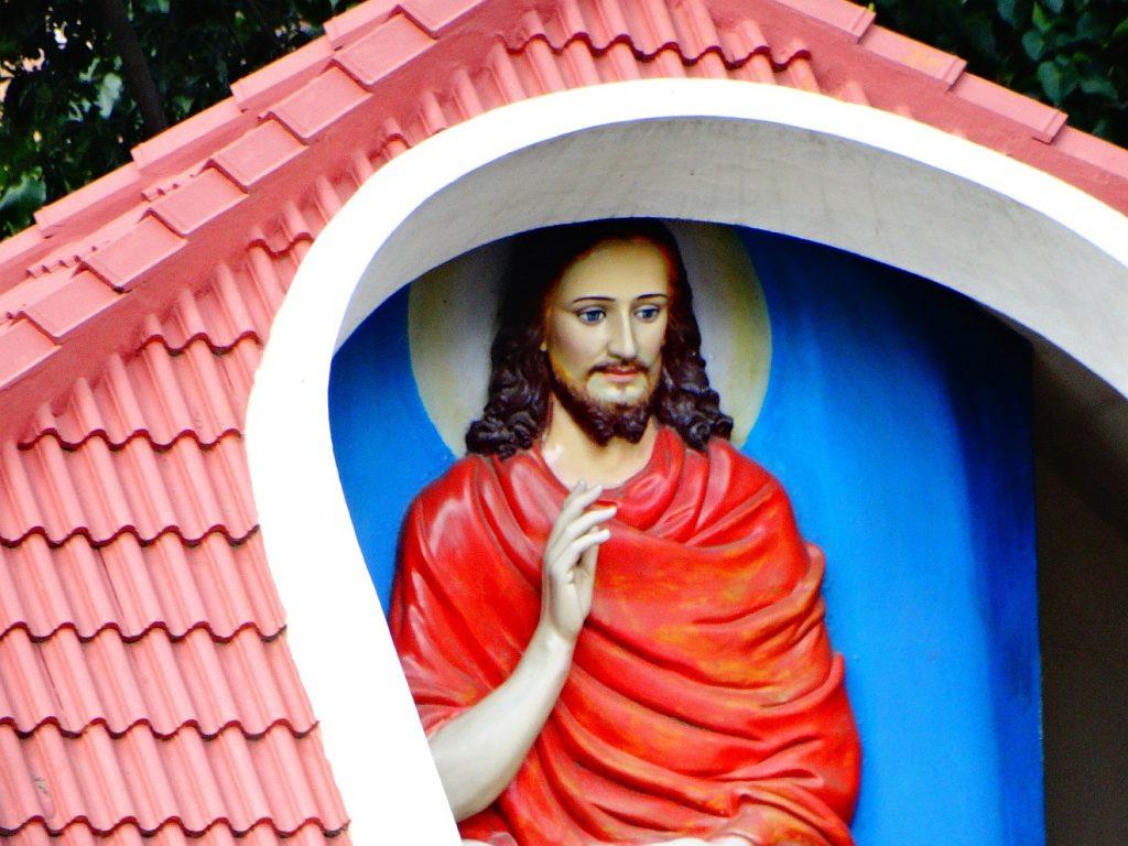 Jesus in rotem Gewand segnet aus einem Torbogen am Straßenrand heraus die Vorübergehenden