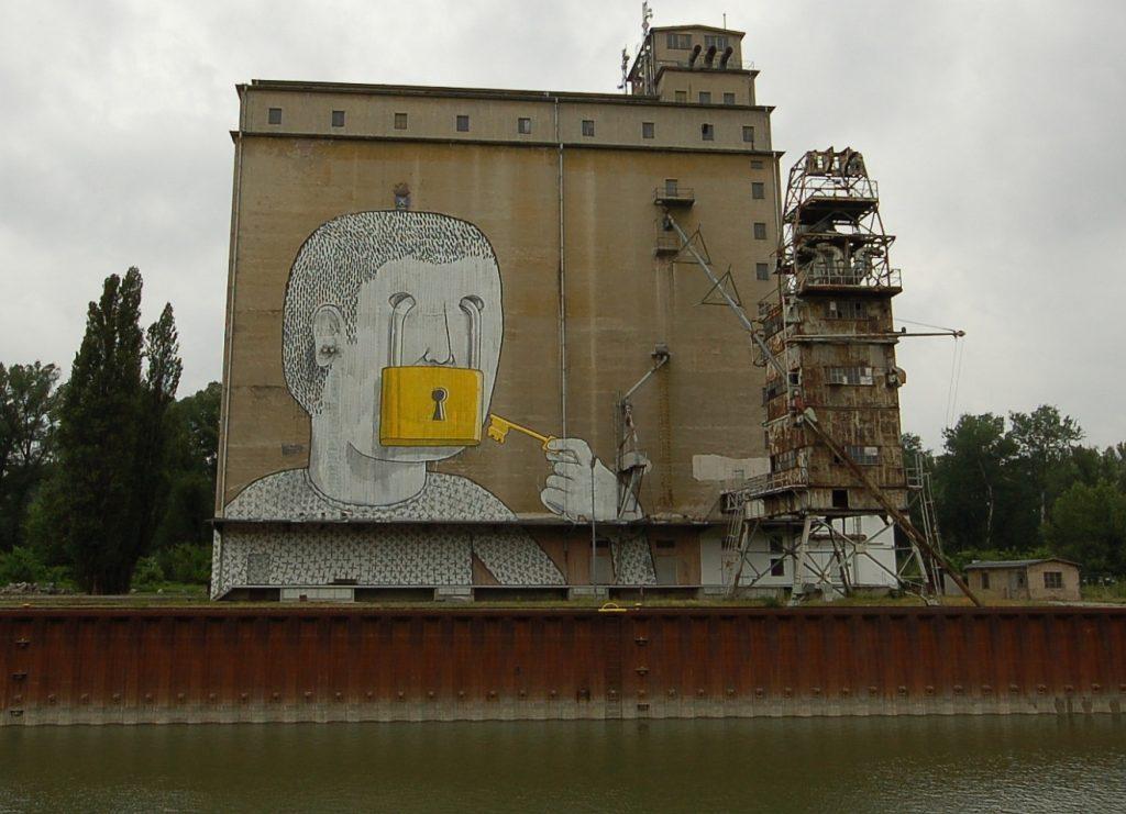 Graffito an einem Hafengebäude: Ein Mann mit einem Vorhängeschloss vor dem Mund, das er selbst ab- oder aufschließen kann