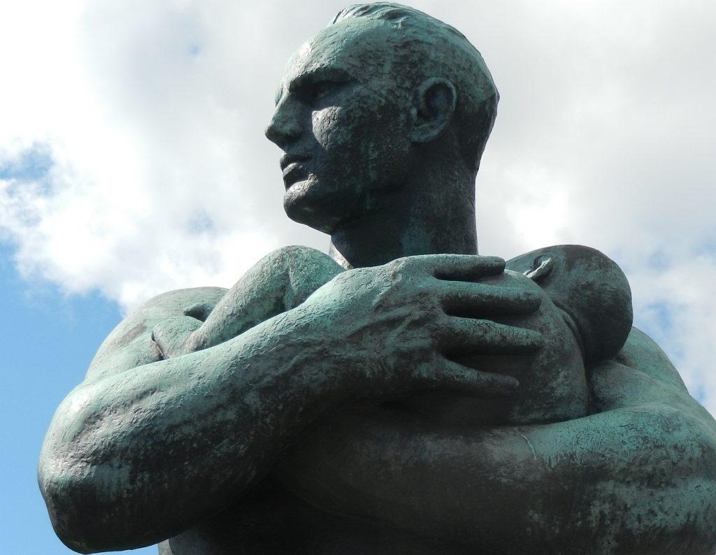 Skulptur eines starken Vaters mit nacktem Oberkörper, der ein kleinen Kind in den Armen hält - so ist Gott - God is Dad!