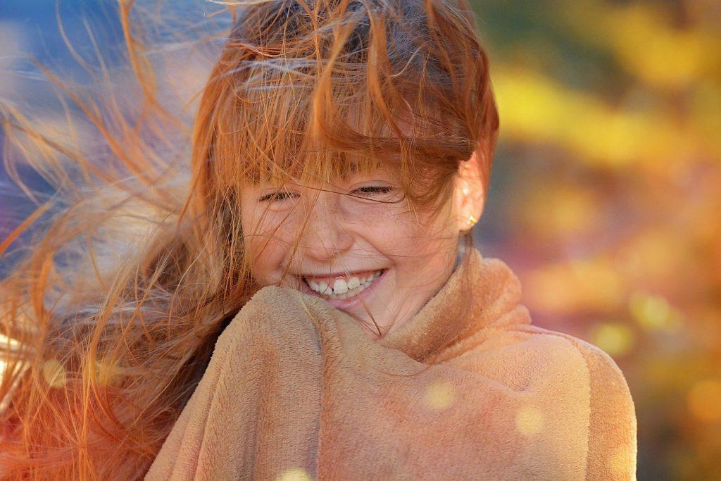 Mädchen mit verwuschelten Haaren, dem der Wind ins Gesicht bläst: wie neugeboren!
