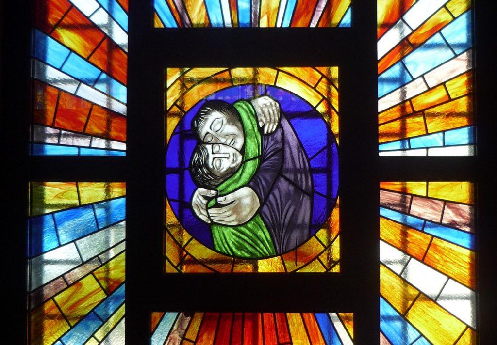 Kirchenfenster mit einem der bekanntesten Gleichnisse Jesu: der Verlorene Sohn wird vom Vater wieder in die Arme geschlossen