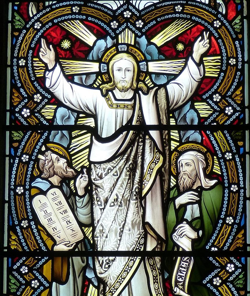 Ein Kirchenfenster zeigt Jesus mit segnend ausgebreiteten Händen und neben ihm Mose mit den Zehn Geboten und der Prophet Elia