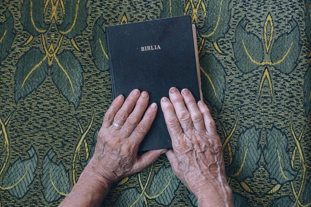 Die Beispiele der Alten: Die Hände einer alten Frau auf einer alten Bibel