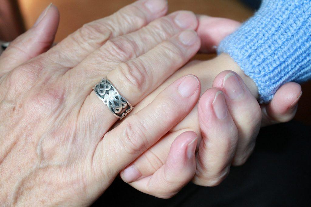 Die Hand einer alten Frau und die Hand eines Kindes