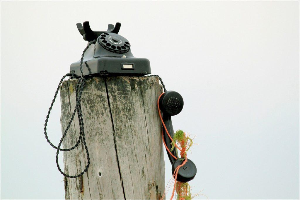 Fürchte dich nicht: Ein altes Telefon steht auf einem hölzernen Poller, vielleicht an einem Strand, der Hörer hängt, an bunten Fäden gehalten, herunter