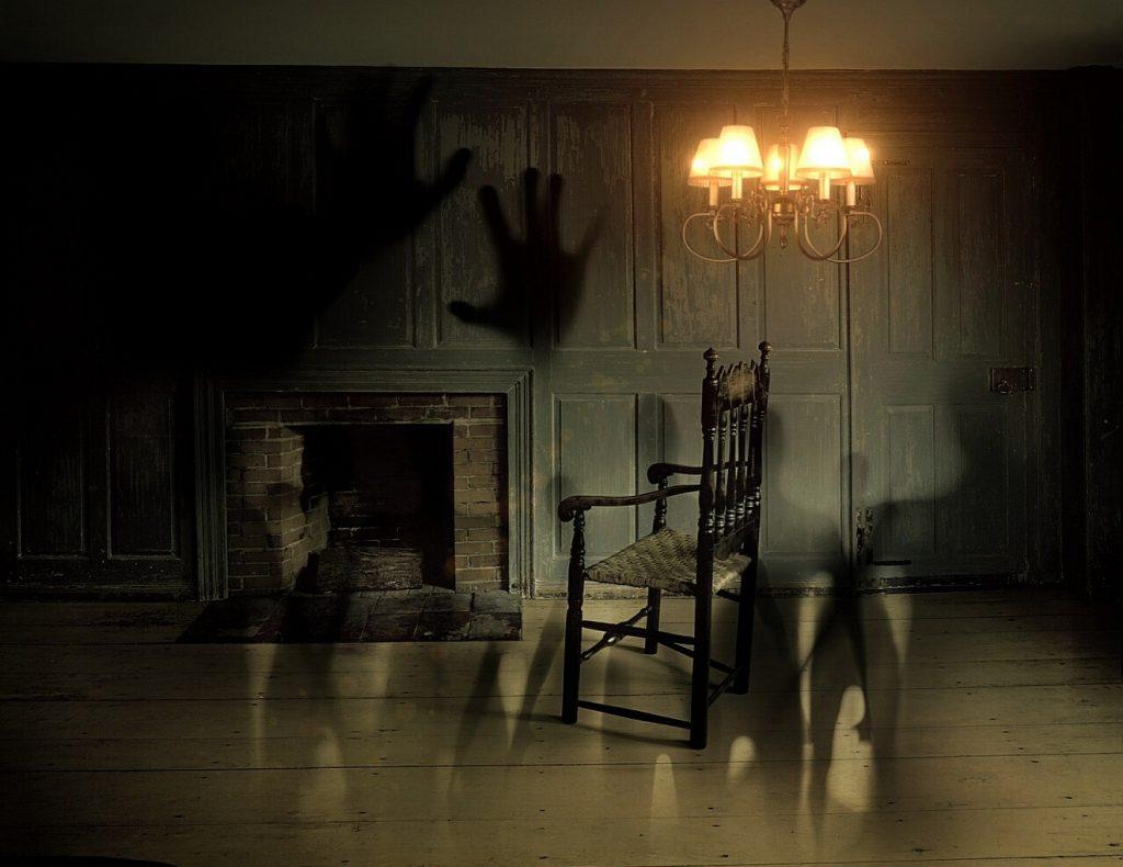 Ein nur mäßig erleuchtetes Zimmer mit Stuhl vor einem Kamin ohne Feuer mit Schatten von Menschen und Händen auf dem Fußboden und an der Wand