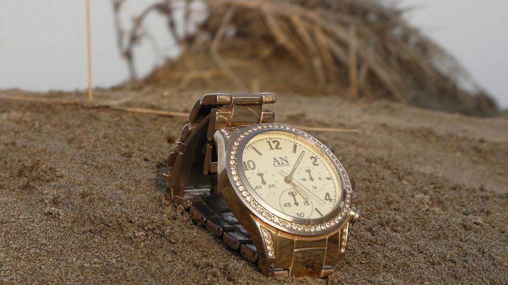 Symbol der Vergänglichkeit der Zeit: eine Armbanduhr im Sand