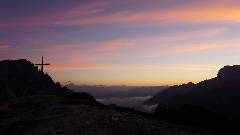 Die Todesnacht kennt ein Morgen: Morgendämmerung in den Bergen mit einem Kreuz an der Seite
