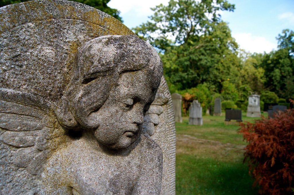 Blickrichtungen auf dem Friedhof: Ein nachdenklicher Friedhofsengel mit gesenktem Blick