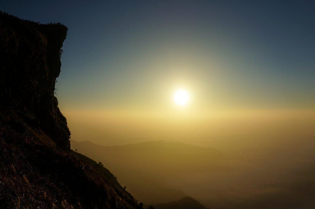 Gott in Ehrfurcht lieb haben: Ein Blick an einem hohen Felsen vorbei zur im Dunst über einem hellgelben Wolkenmeer leuchtenden Sonne