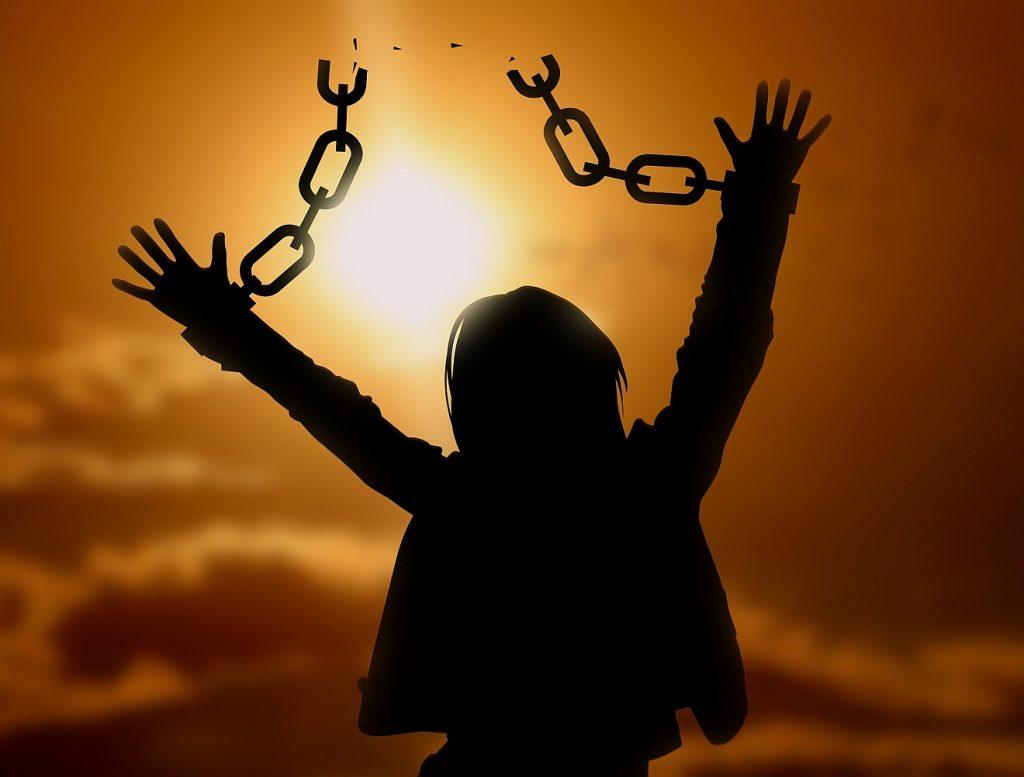 Erlösung der Gefangenen zur Liebe: Eine Gestalt im Gegenlicht mit nach oben zur Sonne hin ausgestreckten Händen, zwischen denen eine Kette zerbrochen worden ist.