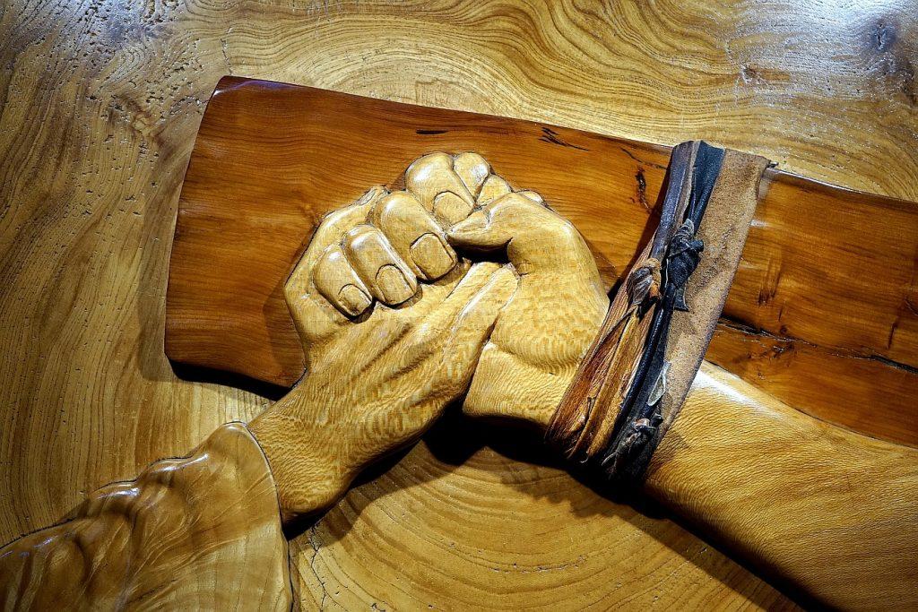 Worte, die die Seele erreichen: Jesu am Kreuz gefesselte Hand hält die Hand, die wir zu ihm ausstrecken