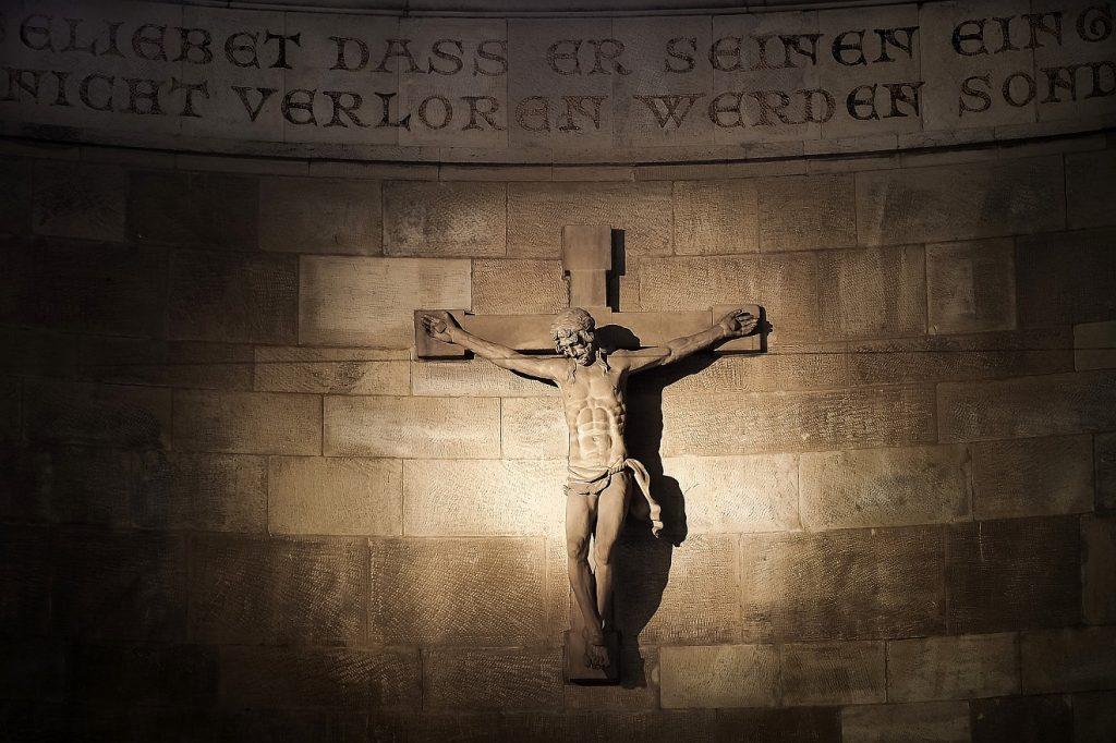 Jesus als Fundament des Glaubens: ein Kruzifix mit dem Körper Jesu an einer Wand aus Steinquadern