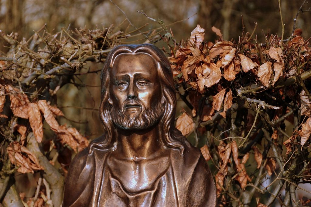 Wachset in der Gnade: Eine Christusfigur, fotografiert vor einem Zaun oder einer Hecke mit braunem Herbstlaub