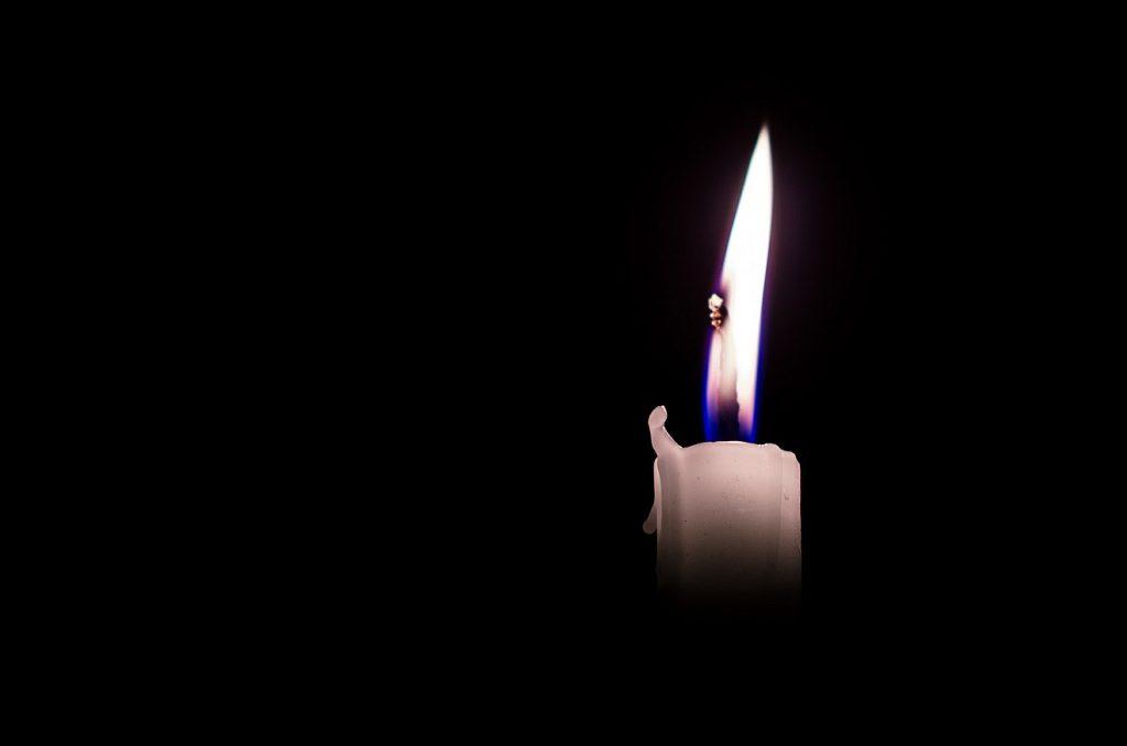 Auch Gott ist traurig: eine Kerze brennt im Dunkeln
