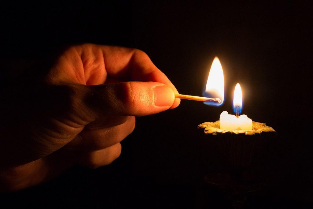 Eine Hand mit einem Streichholz, mit der sie eine kleine Kerze in der Dunkelheit angezündet hat.