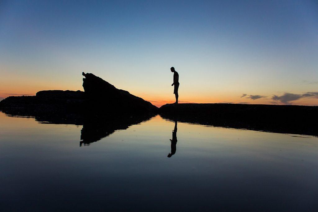 Nicht viele Worte machen: Die Silhouette eines Mannes am Wasser unter einem klaren Abendhimmel