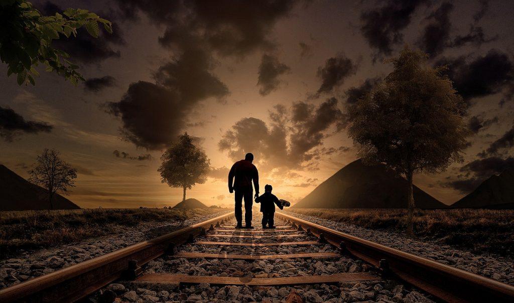 Ein Vater mit seinem Sohn als Schattenriss vor einem bewölkten Abendhimmel in bräunlichen Farbtönen