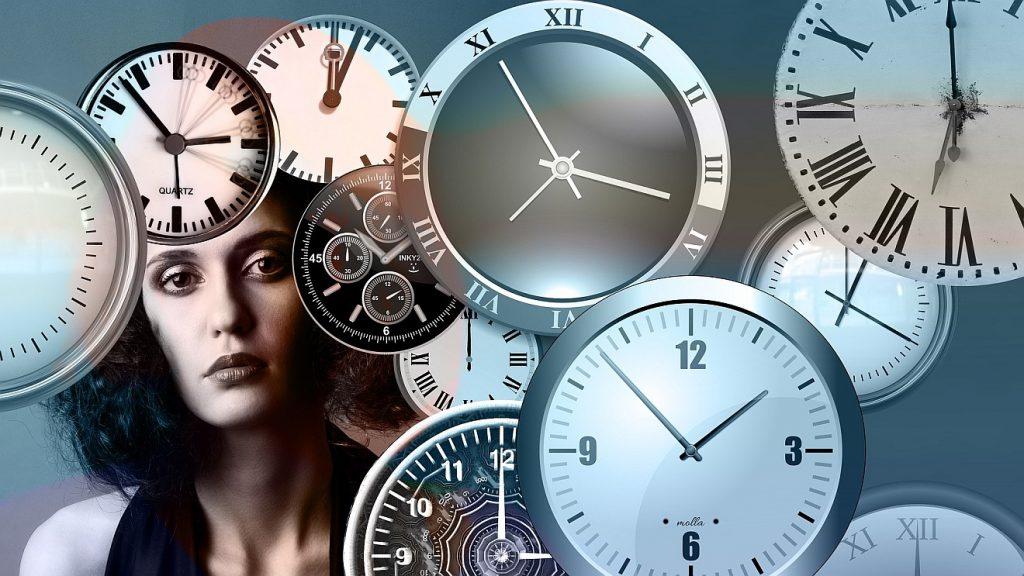Fluch der Vergänglichkeit: Das skeptisch blickende Gesicht einer Frau inmitten von Ziffernblättern verschiedenster Uhren