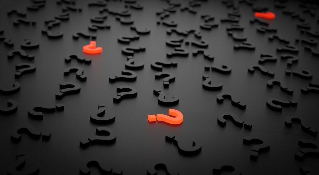 Bittere Fragen: Viele schwarze und einige rote Fragezeichen liegen verstreut auf einem schwarzen Boden