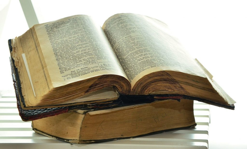 Sich halten nach Gottes Worten: Eine zerlesene Bibel liegt auf einem anderen Buch, vielleicht einem Gesangbuch.
