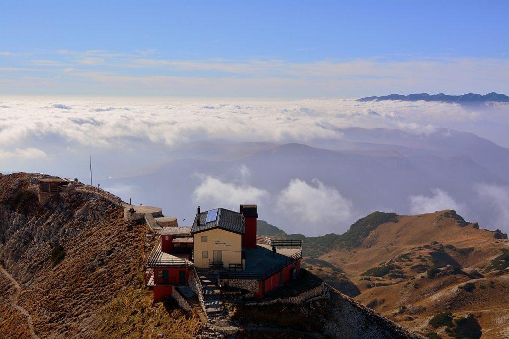 Herr, du bist unsere Zuflucht: Ein Haus in den Bergen vor weißen Wolken, die über einem Tal unter einem blauen Himmel liegen