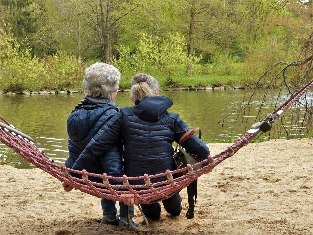 Zwei Todesfälle innerhalb einer Woche in einer Großfamilie: Hier sitzen zwei Frauen auf einer Hängematte an einem Fluss, von hinten gesehen.