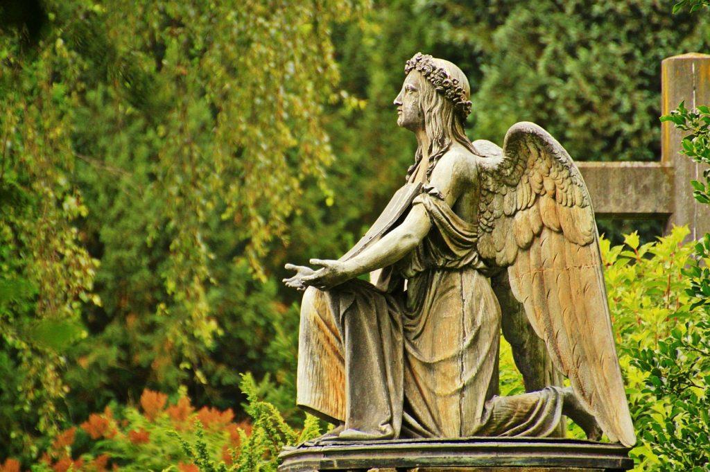 Gott verschmäht unser Gebet nicht: Eine Engelskulptur auf einem Friedhof mit betend vor sich gehaltenen und nach oben geöffneten Händen