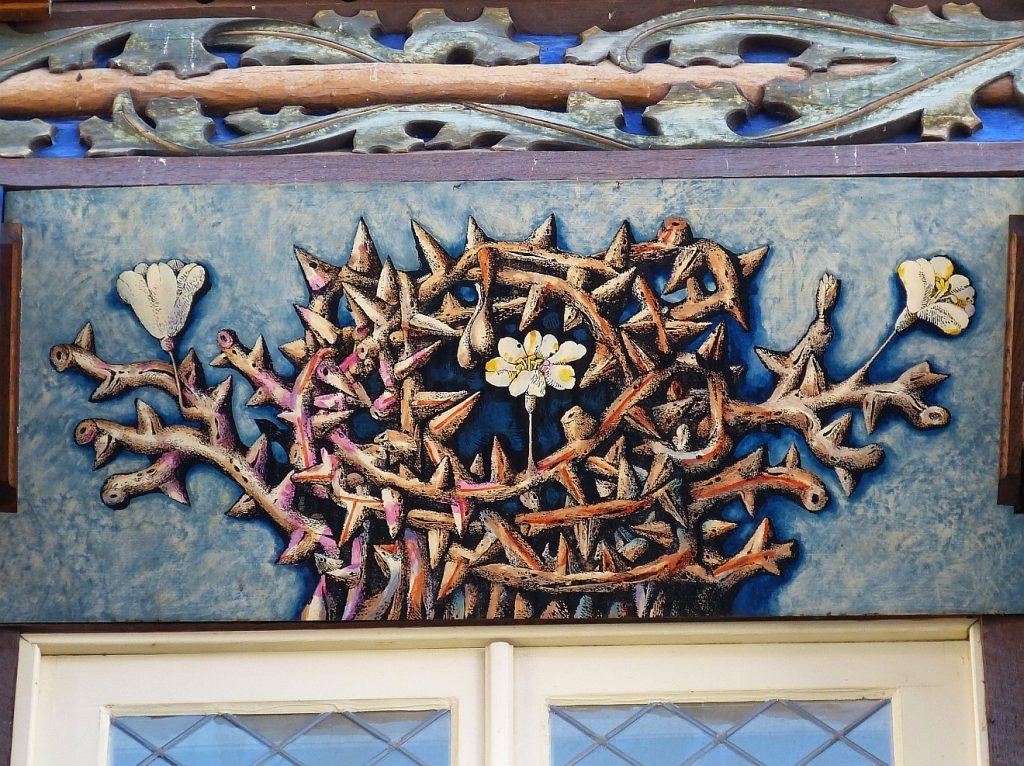 Ehrenkranz des Leidens: Eine blumengeschmückte Dornenkrone an einer Fassade in der Altstadt von Hildesheim