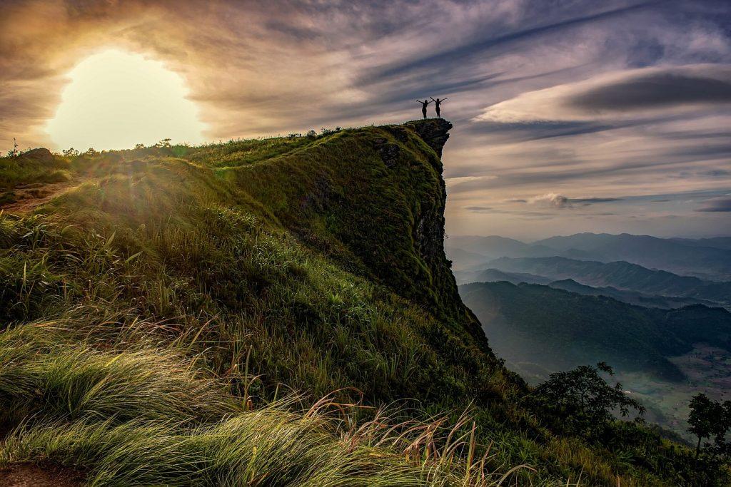 Fröhlich sein unser Leben lang? Zwei Wanderer auf einer Klippe vor eindrucksvollem Himmel freuen sich.