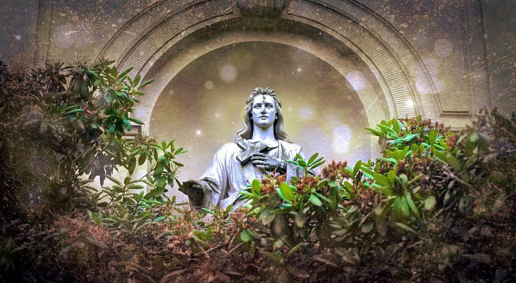 Dem Herrn leben und sterben: Eine Statue von Jesus, der ein Kreuz in der Hand über seine Brust hält, in einem romanischen Bogen hinter Sträuchern